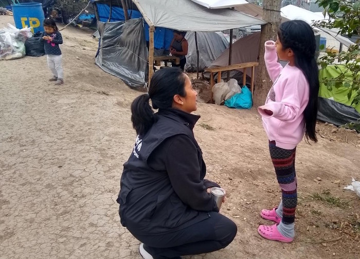 UNICEF Mexico Deputy Representative Pressia Arifin-Cabo kneels down to chat with a child at an encampment in Matamoros in the northeastern state of Tamaulipas.