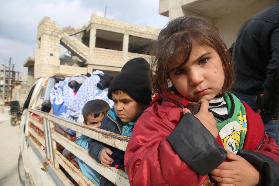 Syrian refugee children flee violence on the back of a truck in the middle of winter.