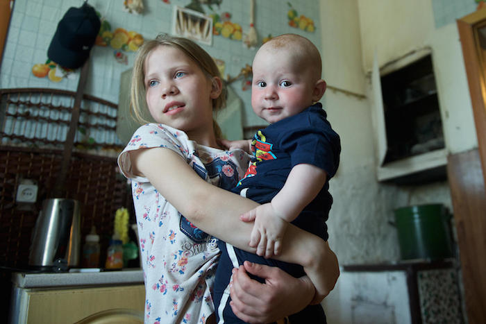 Impoverished families in Kazakhstan like 10-year-old Lyubov's, shown here holding her baby brother Daniil, are recipients of a UNICEF-supported cash assistance program.
