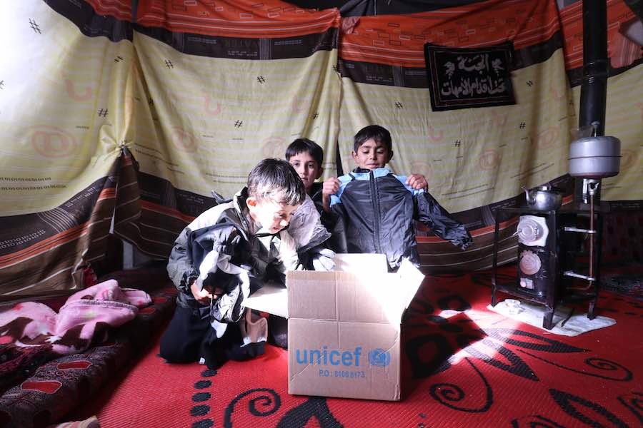 Children peruse the contents of a box full of UNICEF-supported winter supplies in the industrial zone of Hassia in rural Homs in the Syrian Arab Republic on on 7 December 2019.