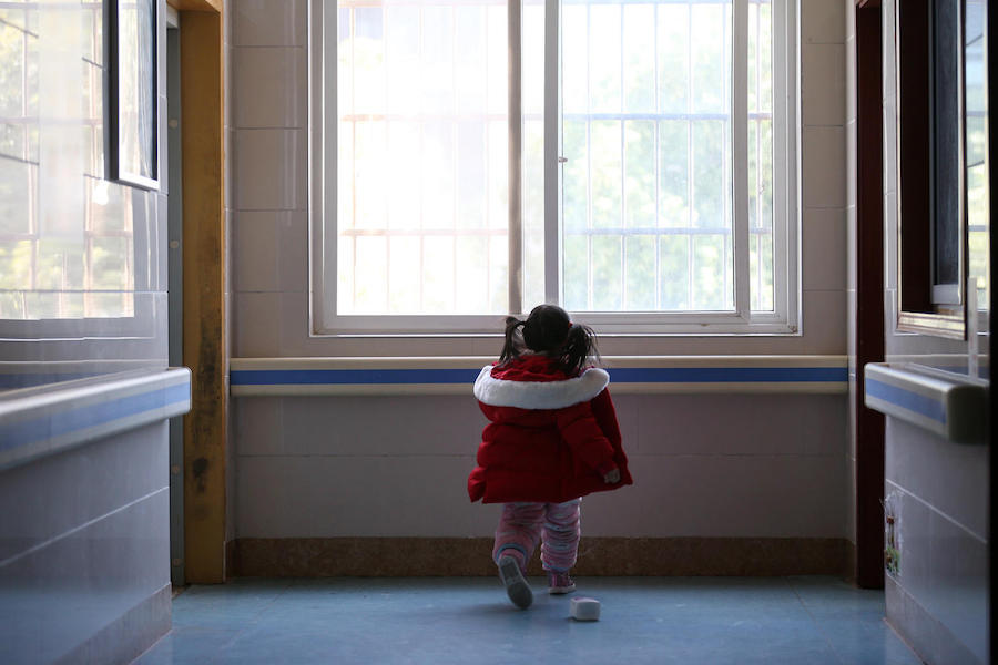Five-year-old Yuanyuan walks the corridor of a hospital affiliated to the Wuhan University of Science and Technology in China on 17 February 2020.
