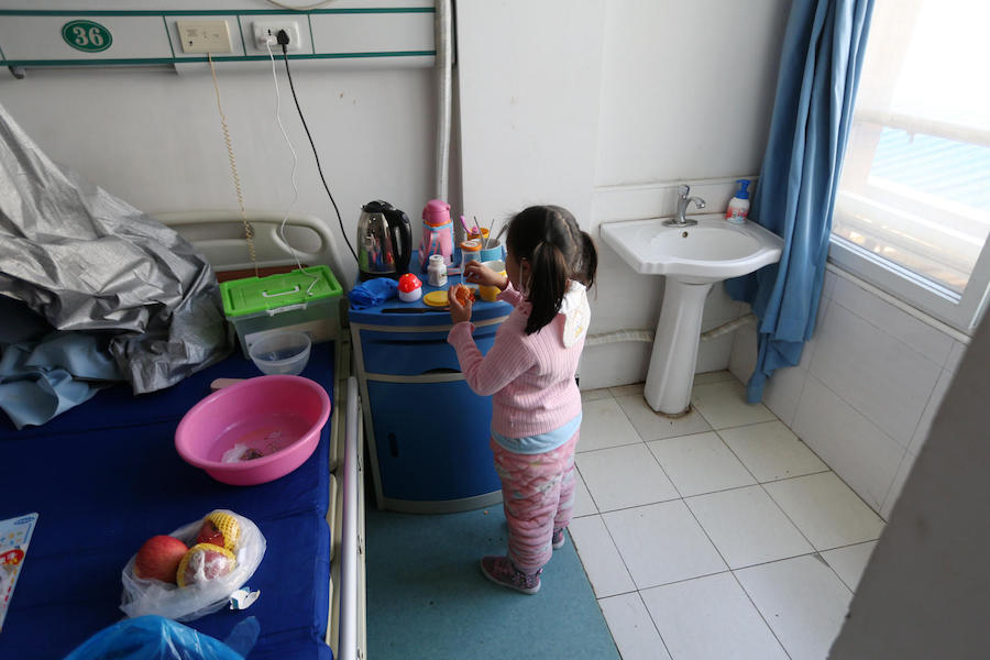 Five-year-old Yuanyuan peels an orange in a ward, where she now lives, in a hospital affiliated with Wuhan University of Science and Technology in China in February 2020.