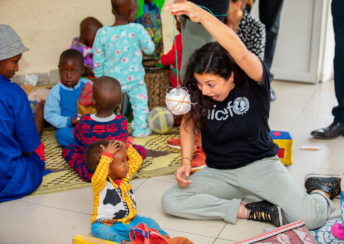 Casey Rotter, founder and managing director of UNICEF NextGen, plays with children at the UNICEF-supported cross-border early childhood development center in Rubavu, Rwanda in 2020.