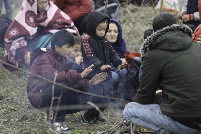 A Syrian family displaced by violence huddles for warmth.
