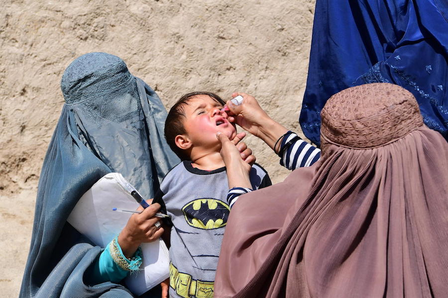 In Kandahar, Afghanistan, a boy is given oral polio vaccine  by UNICEF-supported polio vaccinators.