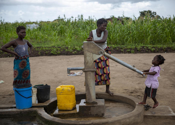 On March 4, 2020, residents of Ndjenja resettlement camp, Mozambique, use a well installed by UNICEF.