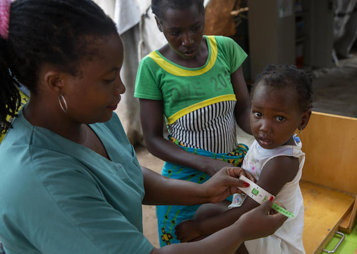 Nurse Madeleina Luis checks children for signs of malnutrition at a UNICEF health center in the Ndjenja resettlement camp, Mozambique, on March 4, 2020.