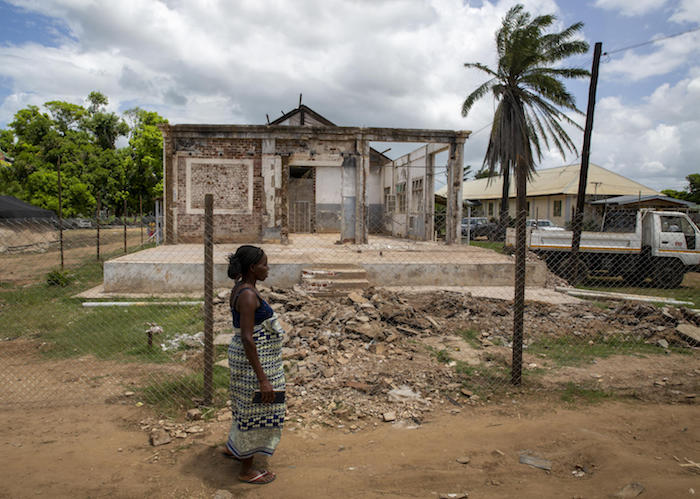 On March 5, 2020, a  woman walks past part of the hospital destroyed by a cyclone in Buzi, Mozambique in 2019.