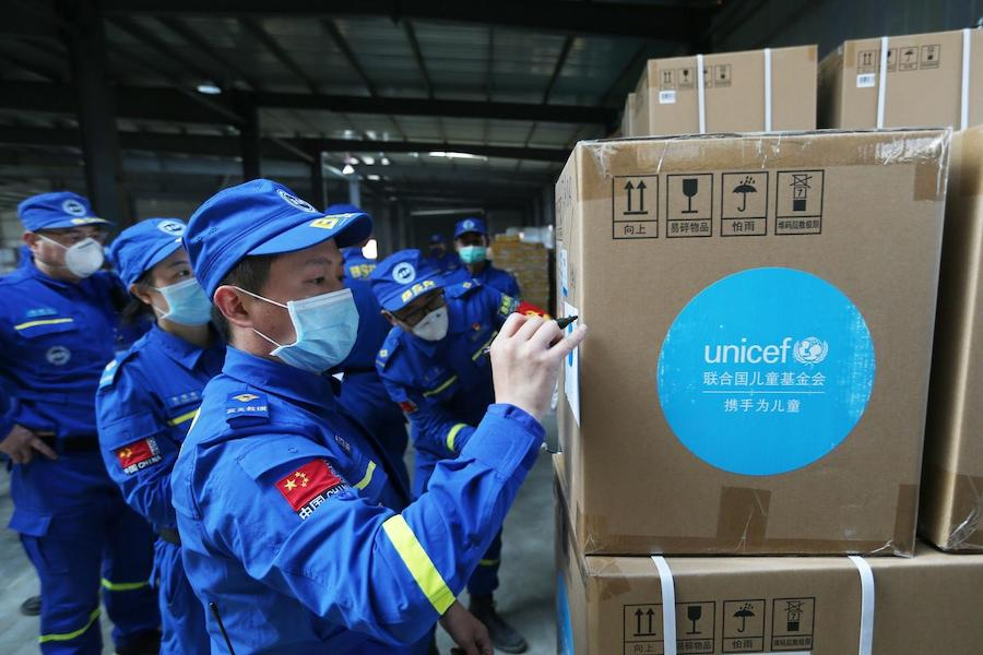 Volunteers check and accept UNICEF donated supplies in an emergency warehouse of the Hubei Charity Foundation in Wuhan, the epicenter of the COVID-19 outbreak, on March 18, 2020.