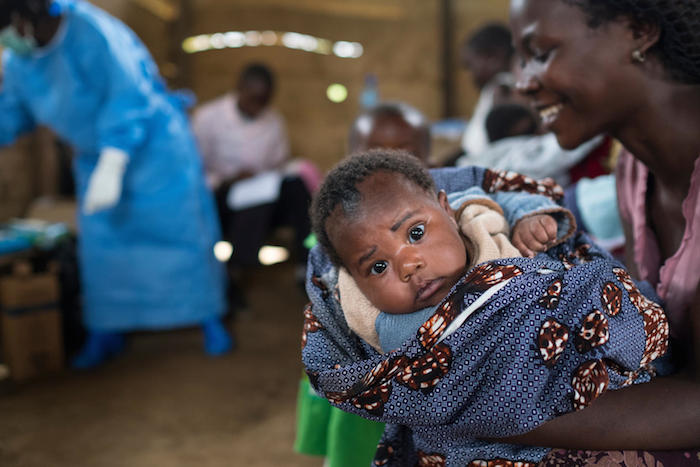 A mother prepares her baby to receive lifesaving vaccines at a UNICEF-supported clinic in the village of Kuka, North Kivu province, DR Congo.