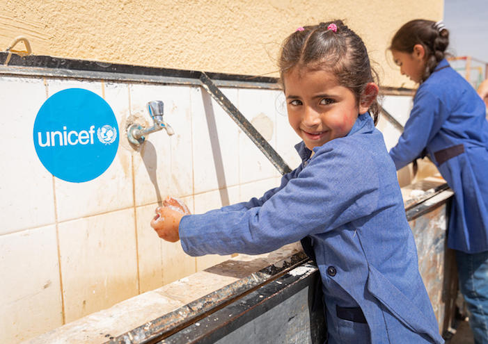 To prevent the spread of the novel coronavirus, Dareen, 6, washes her hands at a wash station set up by UNICEF in Jordan in 2020.