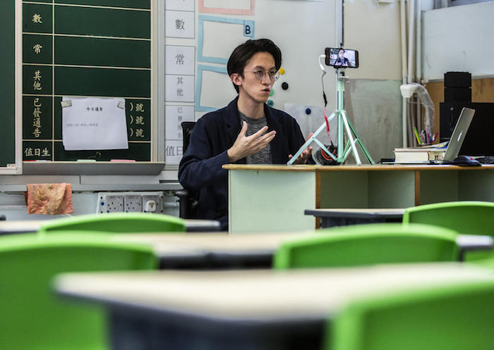 On March 6, 2020, primary school teacher Billy Yeung records a video lesson for his students who have had their classes suspended due to the COVID-19 coronavirus, in his empty classroom in Hong Kong.