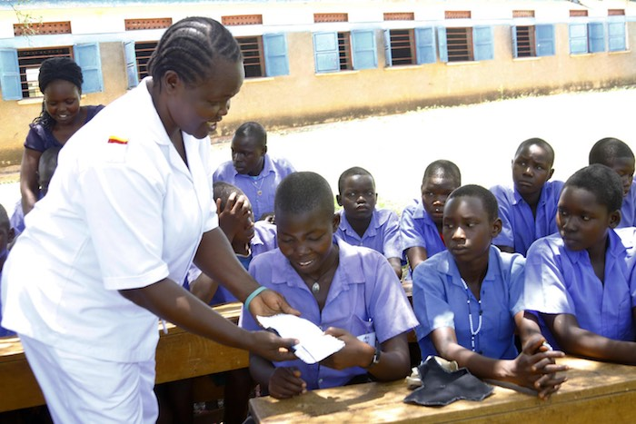Vicky Opia, a Senior Nursing officer from Adjumani hospital who is also a national trainer of adolescents, shows members of the health club of Ajugopi Primary School in Adjumani district how to make re-usable pads during a menstrual hygiene management ses