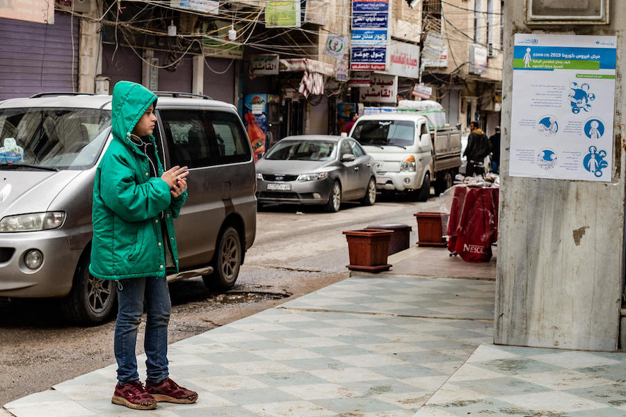 On April 1, 2020, a boy reads a UNICEF poster sharing practical advice on how to prevent the spread of the novel coronavirus in Qamishly, a city of some 250,000 in northeast Syrian Arab Republic.