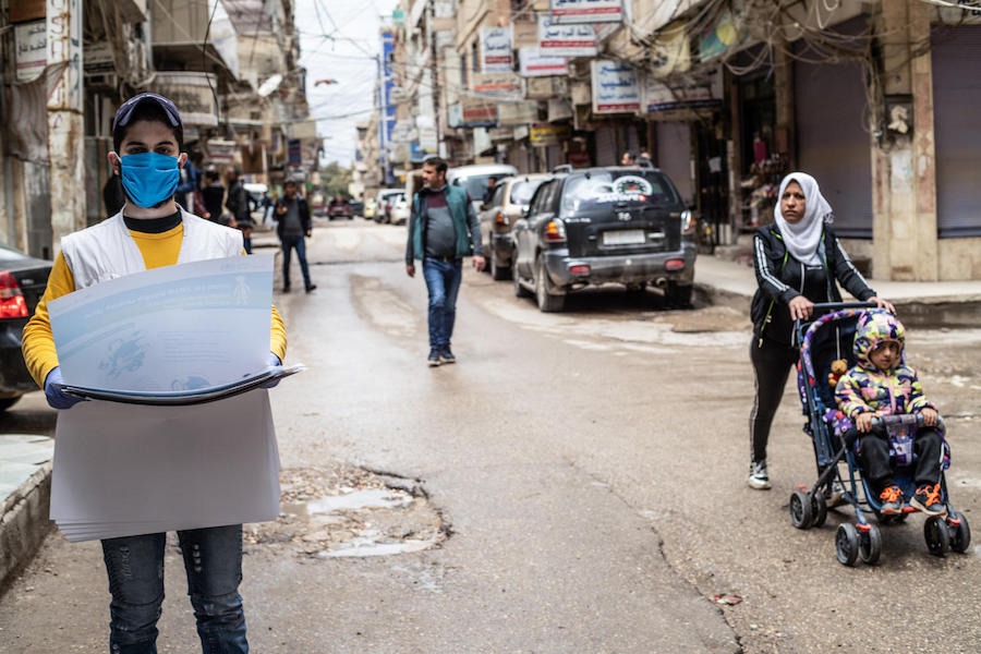 On April 1, 2020, a UNICEF volunteer hangs posters providing important instructions on how to protect against COVID-19 in Qamishly, a city of some 250,000 in northeast Syrian Arab Republic.