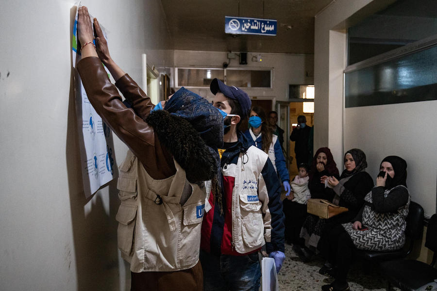 On April 1, 2020, UNICEF volunteers hang posters providing important instructions on how to protect against COVID-19 in a clinic in Qamishly, a city of some 250,000 in northeast Syrian Arab Republic.
