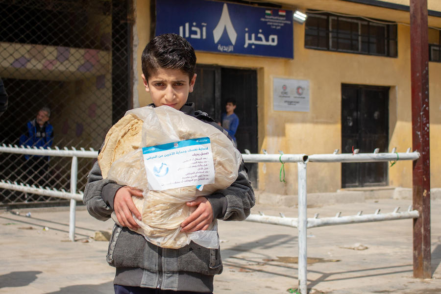 On April 2, 2020, Mohammad, 11, holds a bread bag with a UNICEF label containing messages raising awareness on issues around the 2019 novel coronavirus, in the al-Zebdieh neighborhood of Aleppo, Syrian Arab Republic.