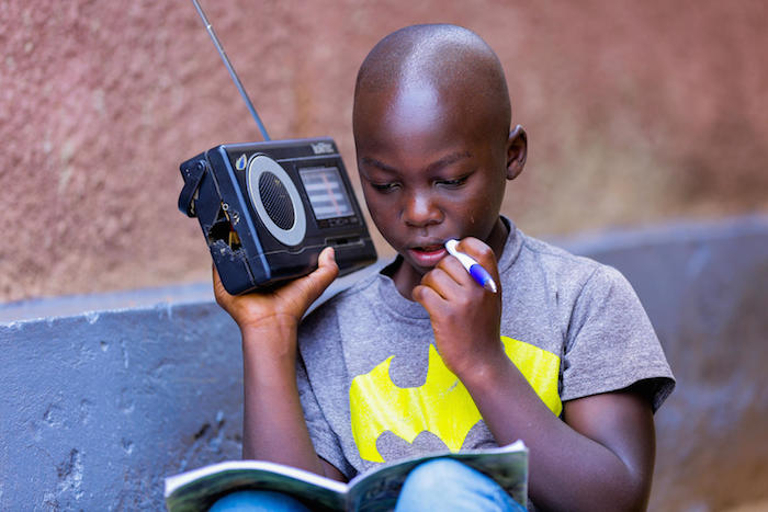An 11-year-old boy in Rwanda whose school has closed in response to COVID-19 listens to his lessons on the radio.