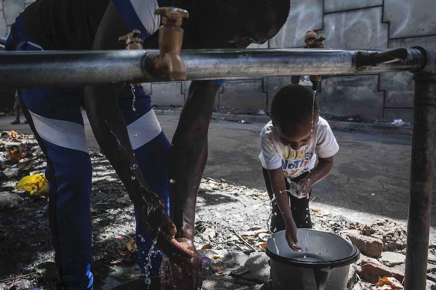 A father and his daughter wash their hands at the informal settlement where they live in Johannesburg, South Africa, where UNICEF is providing water and hygiene supplies to help protect families from the spread of COVID-19.