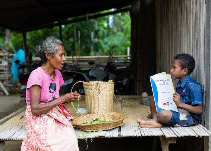 On 14 April 2020, a boy reads as his grandmother looks on in Timor-Leste. The book is part of a series of audio-visual and printed material produced by the Ministry of Education and UNICEF to help children continue learning during the COVID-19 outbreak.