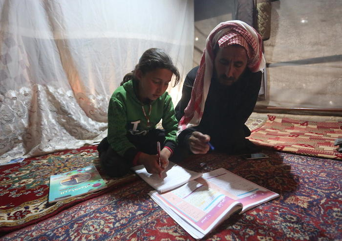 9-year-old Maria and her father follow a pre-recorded lesson on her father's smartphone in a tent at the Kili IDP camp in rural Idlib, Syria.