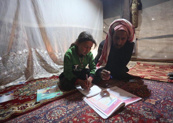On April 9, 2020, 9-year-old Maria follows a pre-recorded lesson on her father's smartphone in a tent at the Kili IDP camp in rural Idlib, Syria.