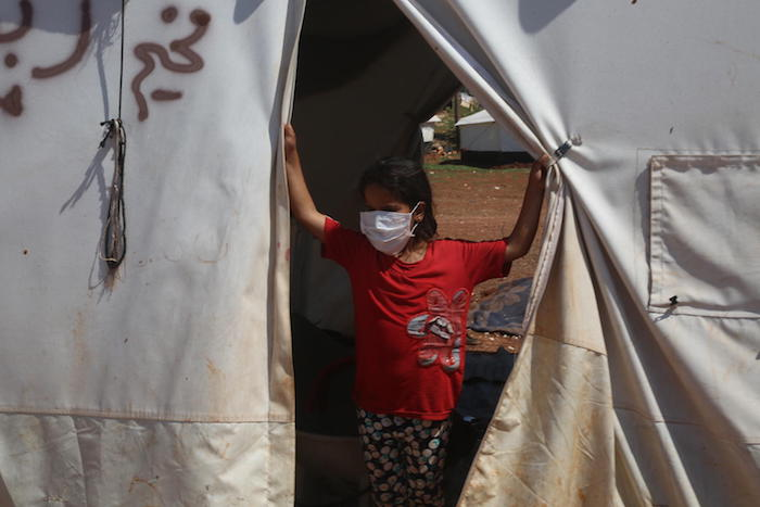 On April 19, 2020, UNICEF volunteers share messaging around staying safe and healthy during the time of the COVID-19 outbreak, in a tent camp for displaced Syrians near the town of Kafr Yahmoul, north of Idlib, Syrian Arab Republic.