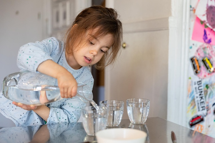 On 19 April 2020, Margot, 4, pours water for her and her parents to have with lunch, at home in New York City, United States of America. Along with more than 1 million other children and youth, Margot has been staying at home with her family since mid-Mar