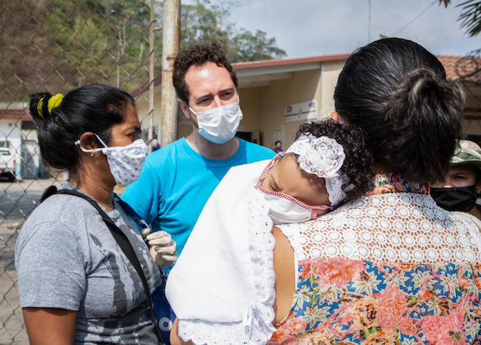 UNICEF water, sanitation and hygiene specialist David Símon talks with women about COVID019 prevention measures at a health clinic on the outskirts of Caracas, Venezuela on April 22, 2020.