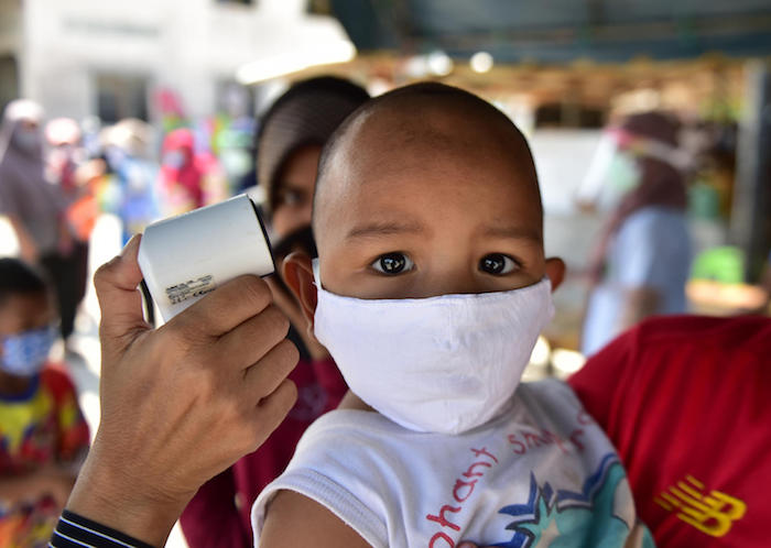 A young child has his temperature checked as people receive food support at a program organized by the Southern Peace Media Club in Thailand's southern province of Narathiwat on April 17, 2020.