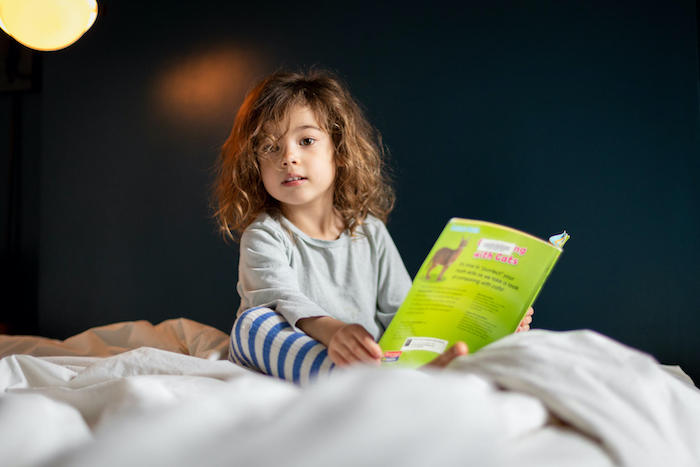 Margot, 4, reads a book at home in New York City, on a weekday she would normally be at daycare.