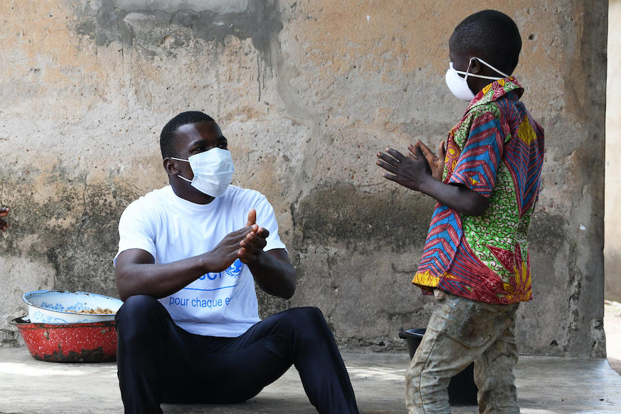 In the village of Morovine, in north Côte d'Ivoire, a UNICEF staff member speaks to a young boy about the importance of washing hands and wearing a face mask to protect against COVID-19.