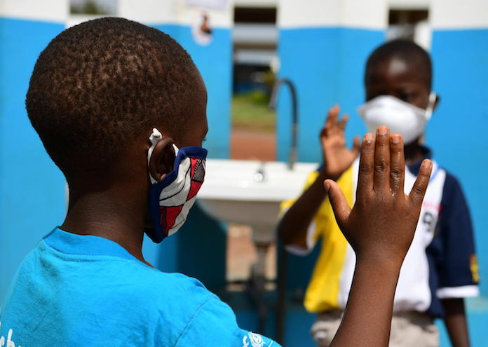 In April 2020, 10-year-old Kolo, left, and his friend Chris, 6, wear masks and wash their hands to prevent the spread of COVID-19 in Korhogo, in the North of Côte d'Ivoire.