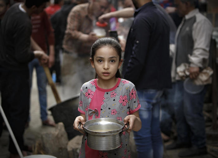On April 24, 2020 in Gaza City, a Palestinian girl carries a portion of soup, given out to families in need during the Islamic holy month of Ramadan, amid the coronavirus COVID-19 pandemic.