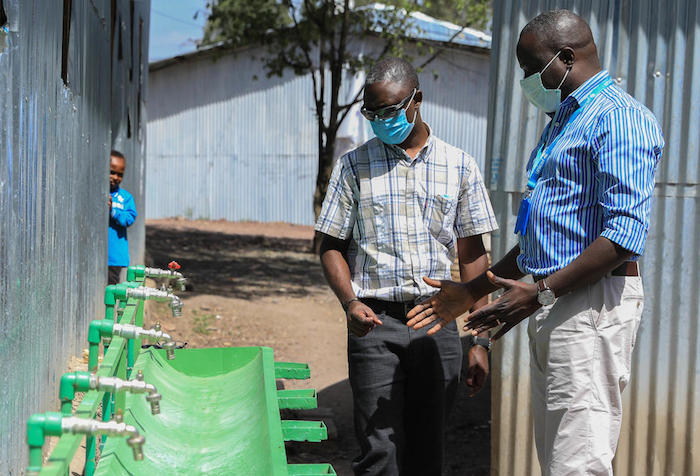 The WASH Chief for UNICEF Ethiopia inspects a hands-free hand washing station designed by a UNICEF WASH engineer.