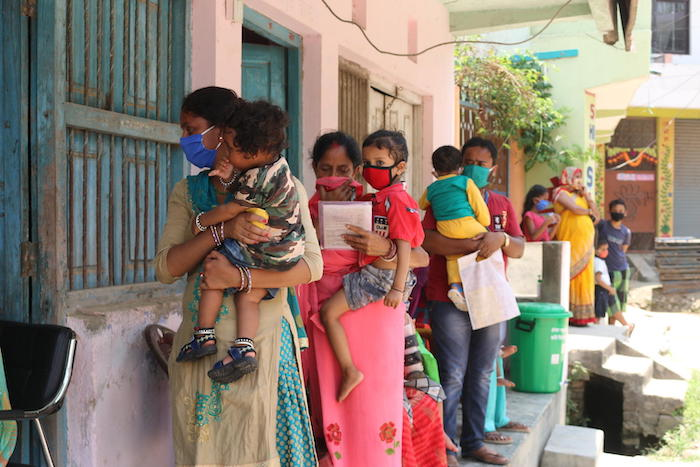 Parents and caregivers line up with their children outside a UNICEF-supported immunization clinic in Janakpur, southern Nepal.