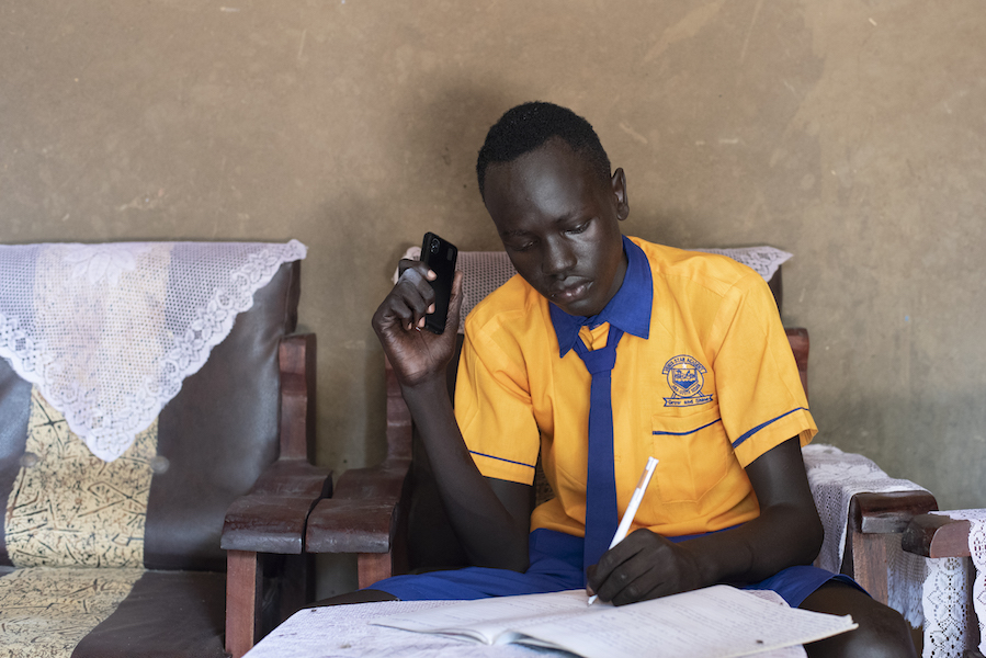 In June 2020 in South Sudan, George, 17, listens to a NICEF-supported radio lesson on his phone while schools are closed to prevent the spread of the novel coronavirus.