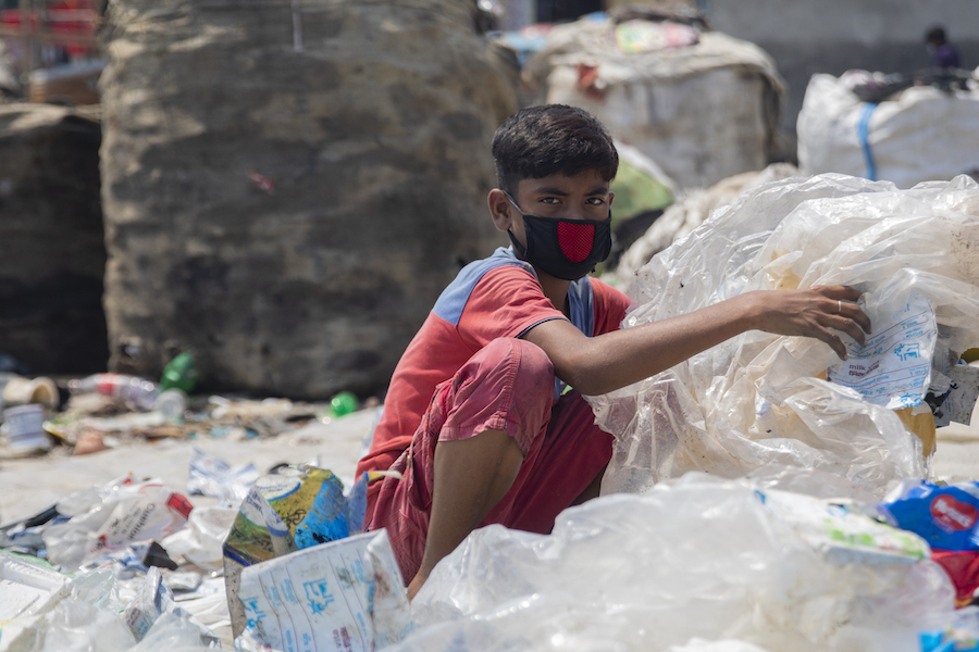 Miajul, 12, sorts through plastic waste at a dump in Shyamol Palli, Dhaka, Bangladesh, looking for material he can sell to recyclers.