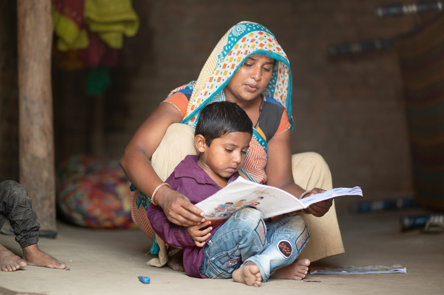 UNICEF supported programs follow up with migrants who have returned to their villages in India. Manguben Patel and her son Vanraj review pre-primary education activity kits for kids during Covid lockdown.