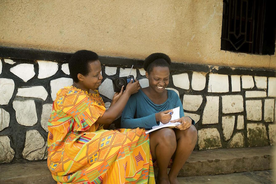 Samantha, 17, listens to radio lessons with her mother, Kayirangwa Mary Assoumpta, outside their home in Rwanda.