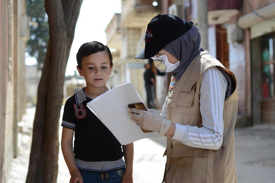On May 14, 2020, UNICEF-supported volunteer Aya, 24, talks with a boy about COVID-19 in the war-ravaged village of Teir-Ma'aleh, Homs, Syria.