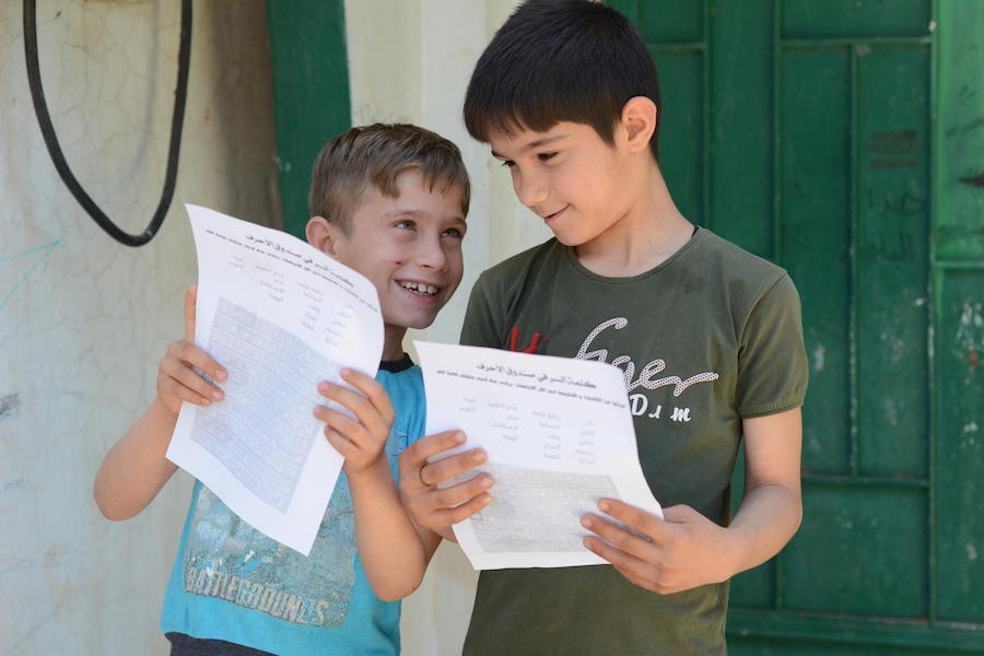 On May 14, 2020, children check paper exercises brought to them at home by UNICEF-supported volunteers during COVID-19 lockdown in Teir-Ma'aleh, northern rural Homs, Syrian Arab Republic.