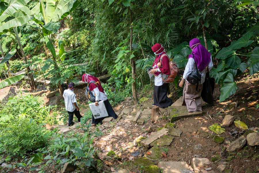 UNICEF-supported nutritionist Dessy Sandra Dewi and colleagues make their way down a steep path to perform home visits to breastfeeding mothers in Paseban Village, Bayat, Klaten, Indonesia.