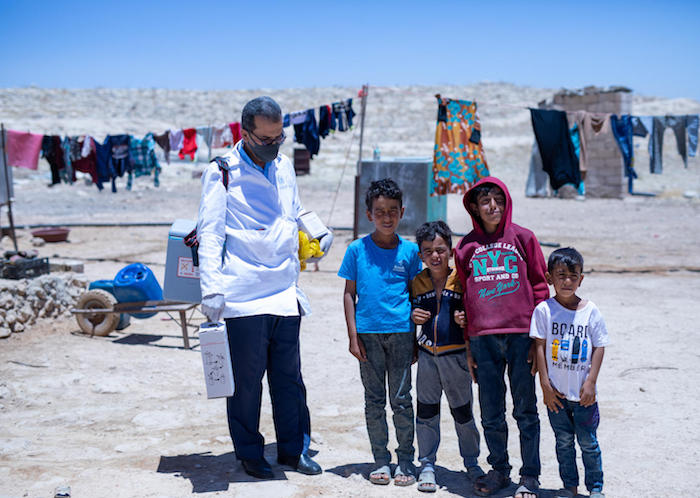 On 23 June 2020, a health worker stands beside a group of boys while conducting a joint UNICEF-WHO vaccination campaign in an informal tented settlement in Zarqa governorate, Jordan.