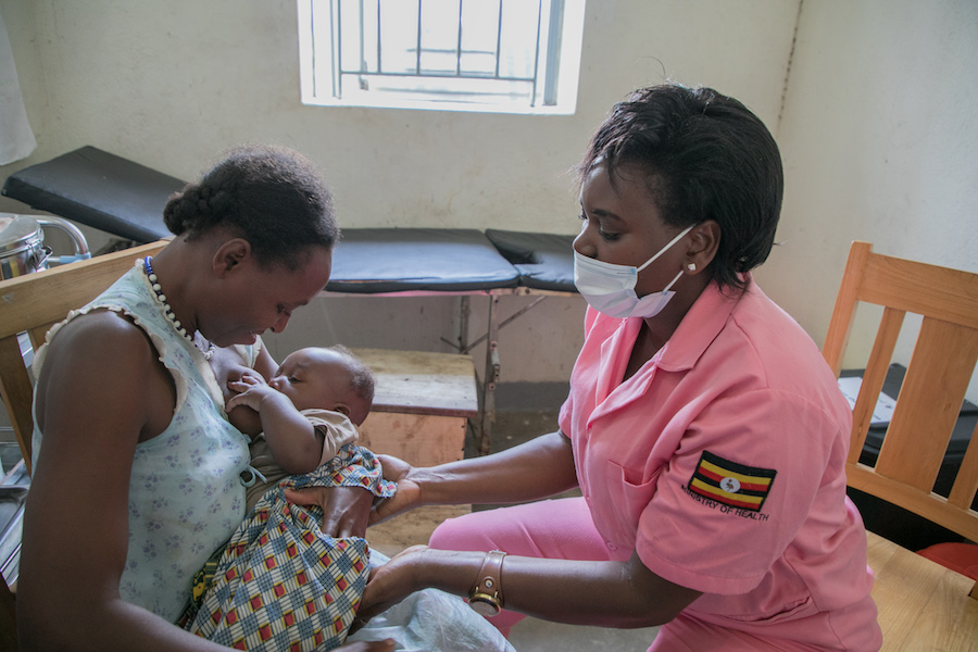 A UNICEF-supported midwife shows a mother best breastfeeding practices at Kasanda Health Center in Uganda in 2020.