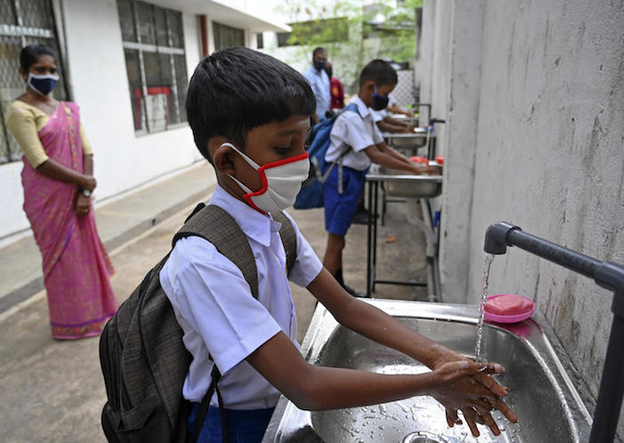 Students wearing facemasks wash their hands inside their school after it was reopened in Colombo, Sri Lanka on 6 July 2020.
