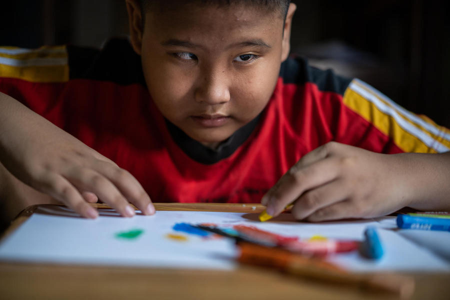 Kevin, 9, a child with a visual impairment, draws with a crayon in his room at home in Banyumas, Central Java, Indonesia.