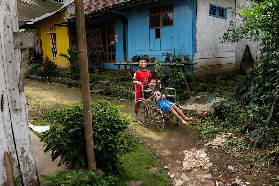 Kevin, 9, a child with a visual impairment, pushes his 12-year-old friend Syaiful's wheelchair as they play outside in Banyumas, Central Java, Indonesia.