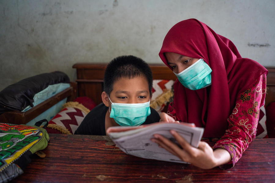 yaiful, 12, a child with a physical impairment, studies with his UNICEF-trained teacher, Fatikhatus, at his grandfather's home in Banyumas, Central Java, Indonesia in 2020..