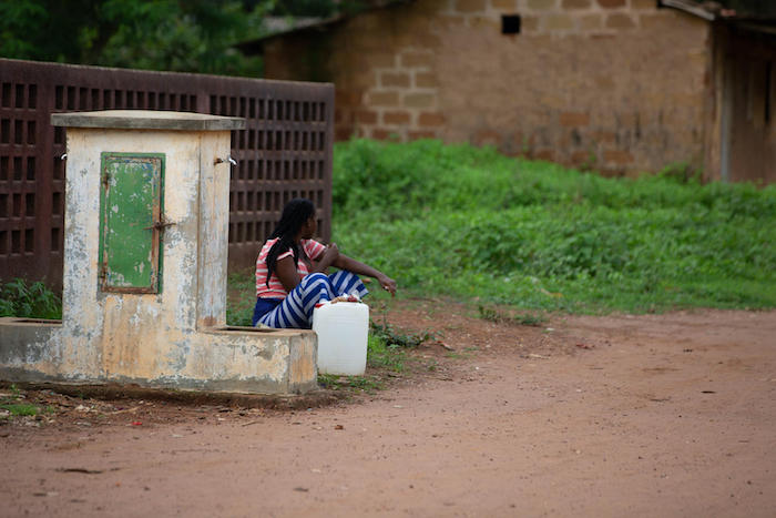 A woman in Koba, Kindia, Guinea, waits to fill her jug with water from a community access point.